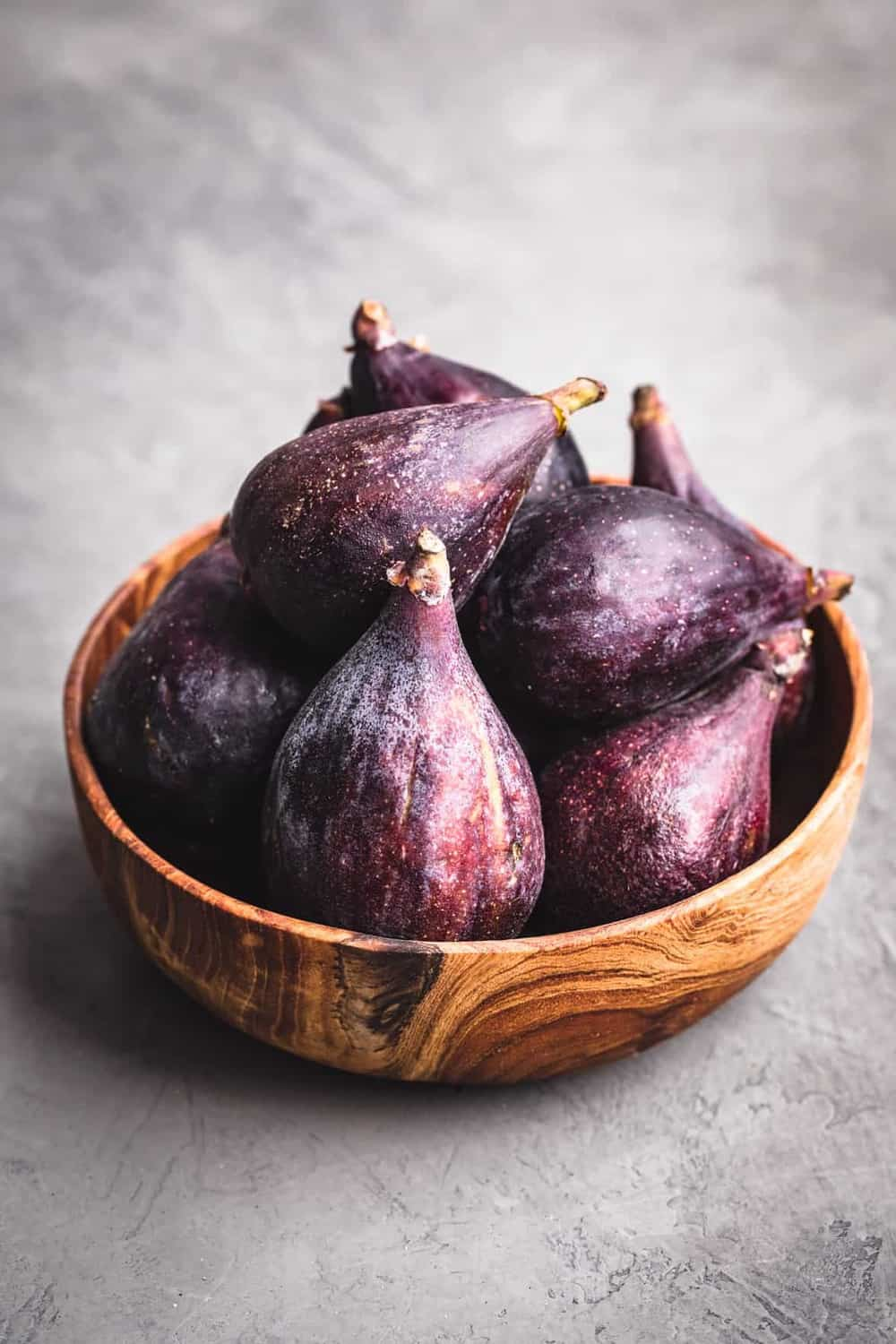 A handfuls or fresh figs, in a wooden bowl, with a grey background.