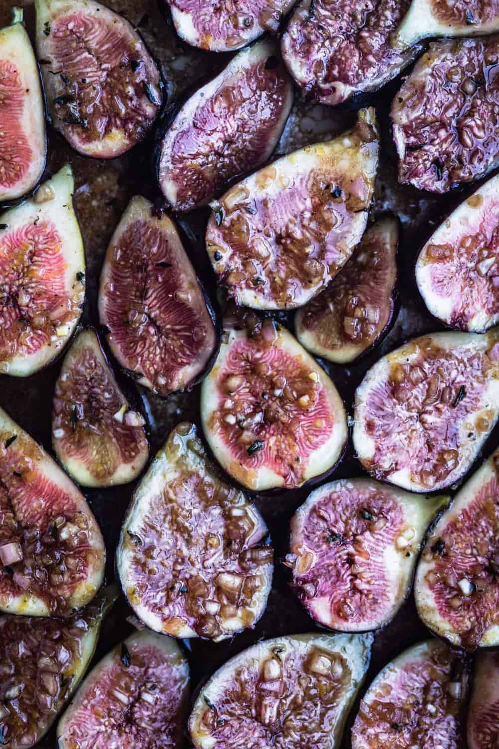 Figs cut in half, skin side down, up close, marinating in the vinaigrette, ready to go in the oven.