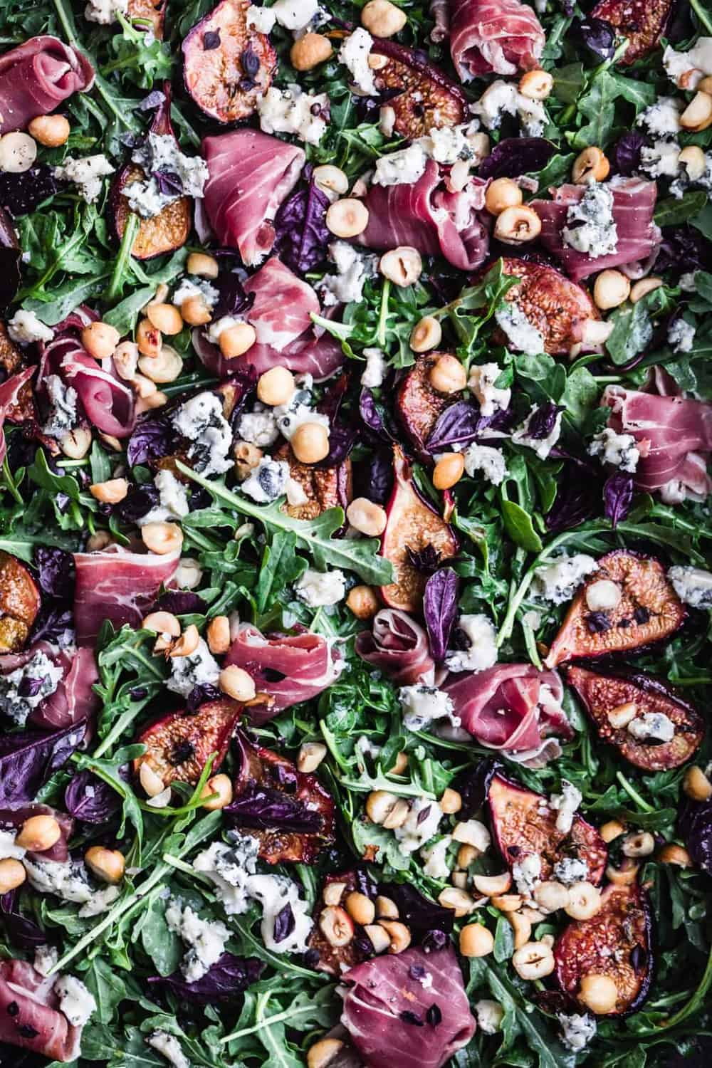 Caramelized Fig & Prosciutto Salad with hazelnuts, basil, blue cheese and arugula. Overhead shot. Up close.