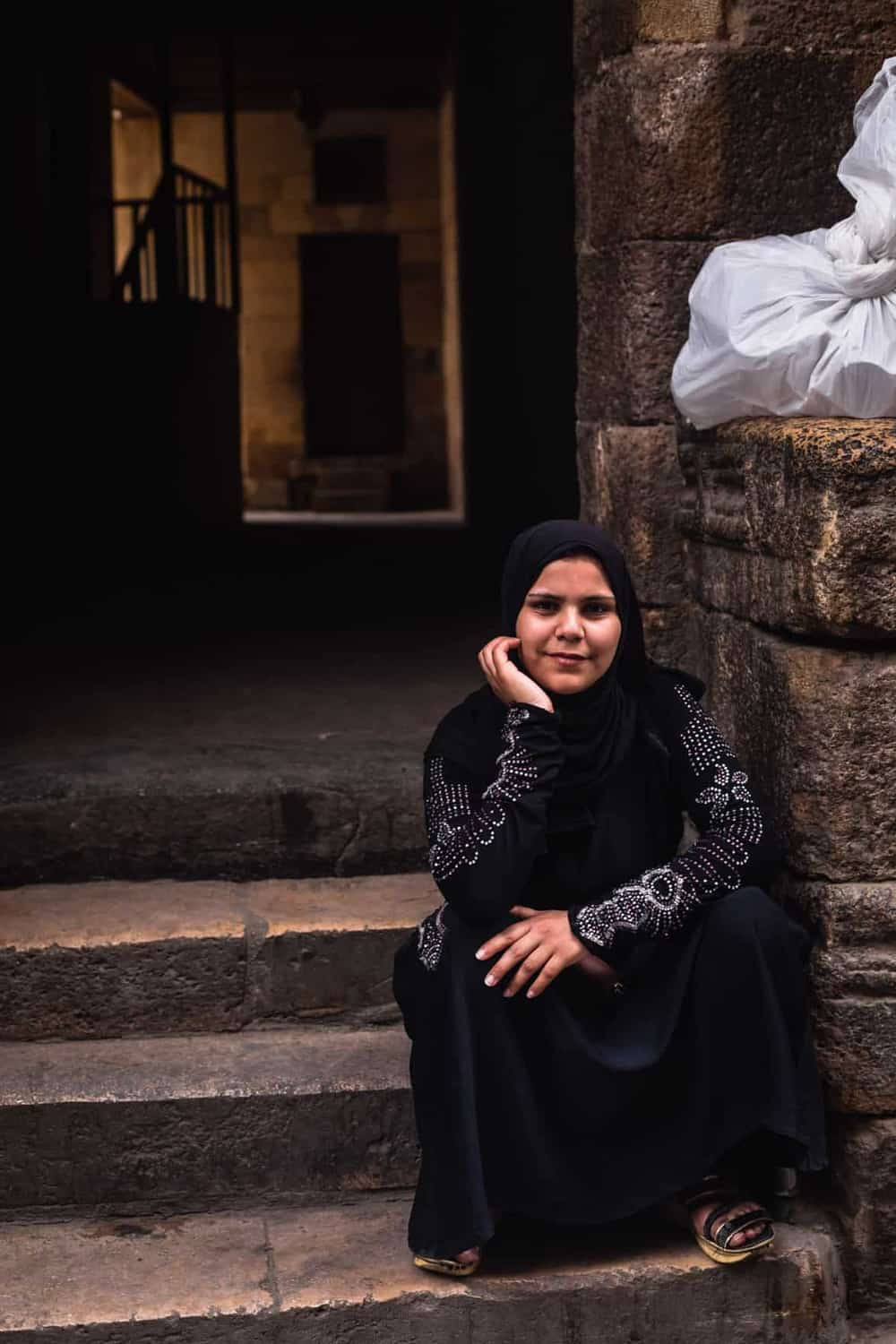 portrait shot of woman in Old Black with a headscarf posing for me with a serious face in Old Cairo.