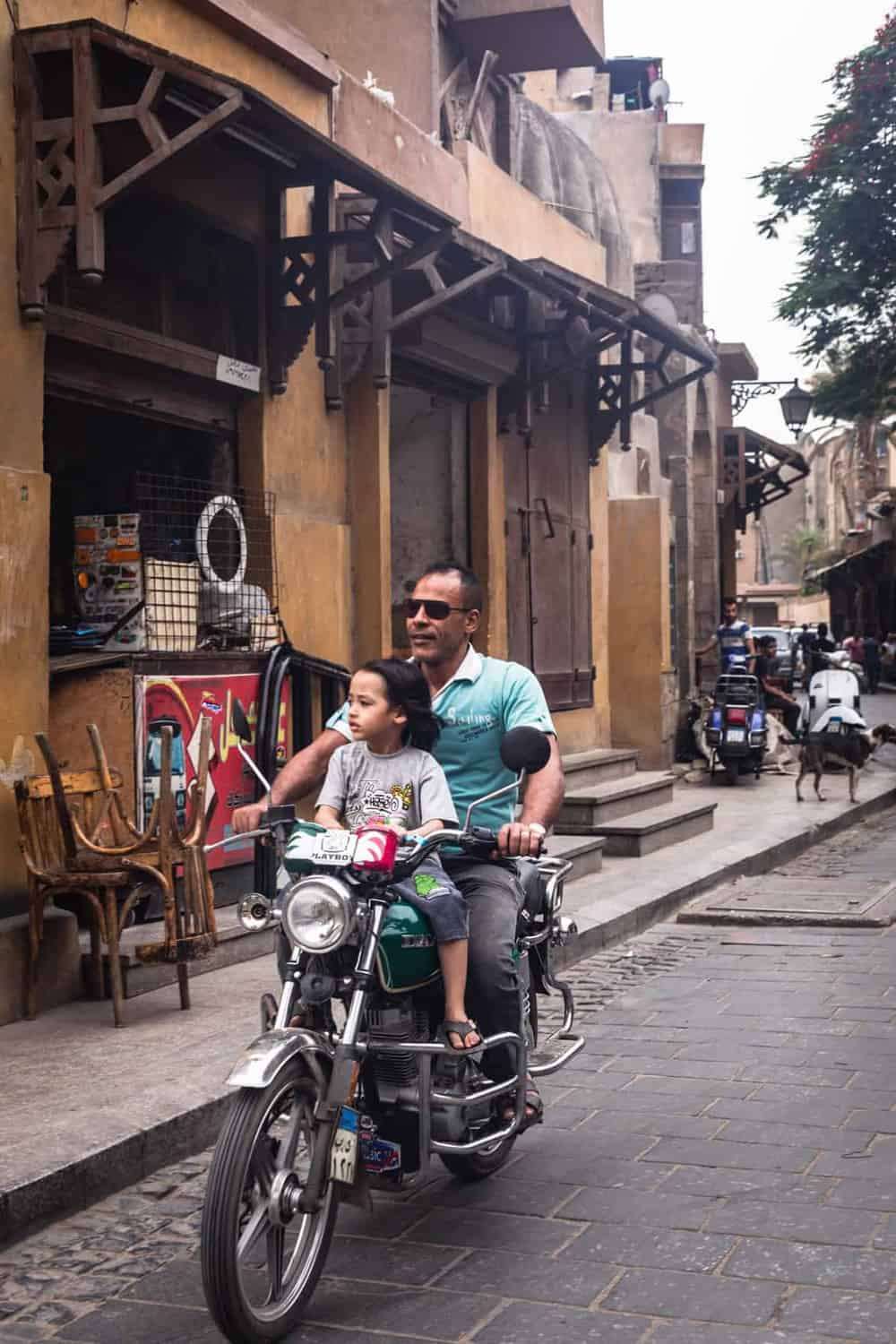 Father and son riding an moped in Old Cairo.