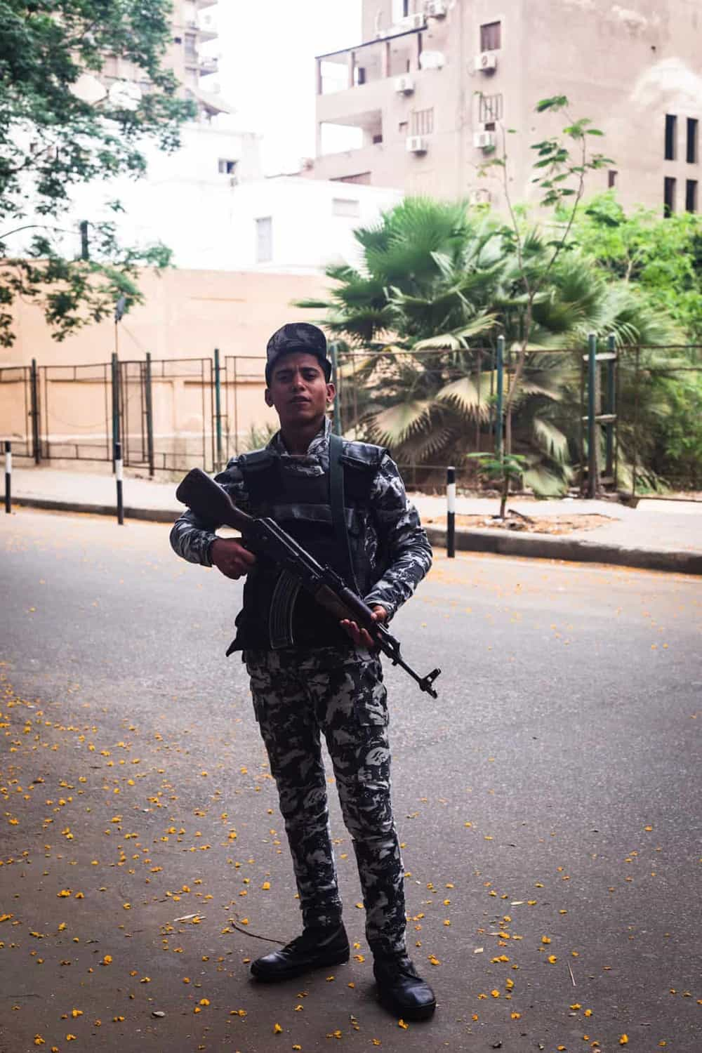 Portrait shot of a security guard proudly posing with his gun in the Zamalek district of Old Cairo.