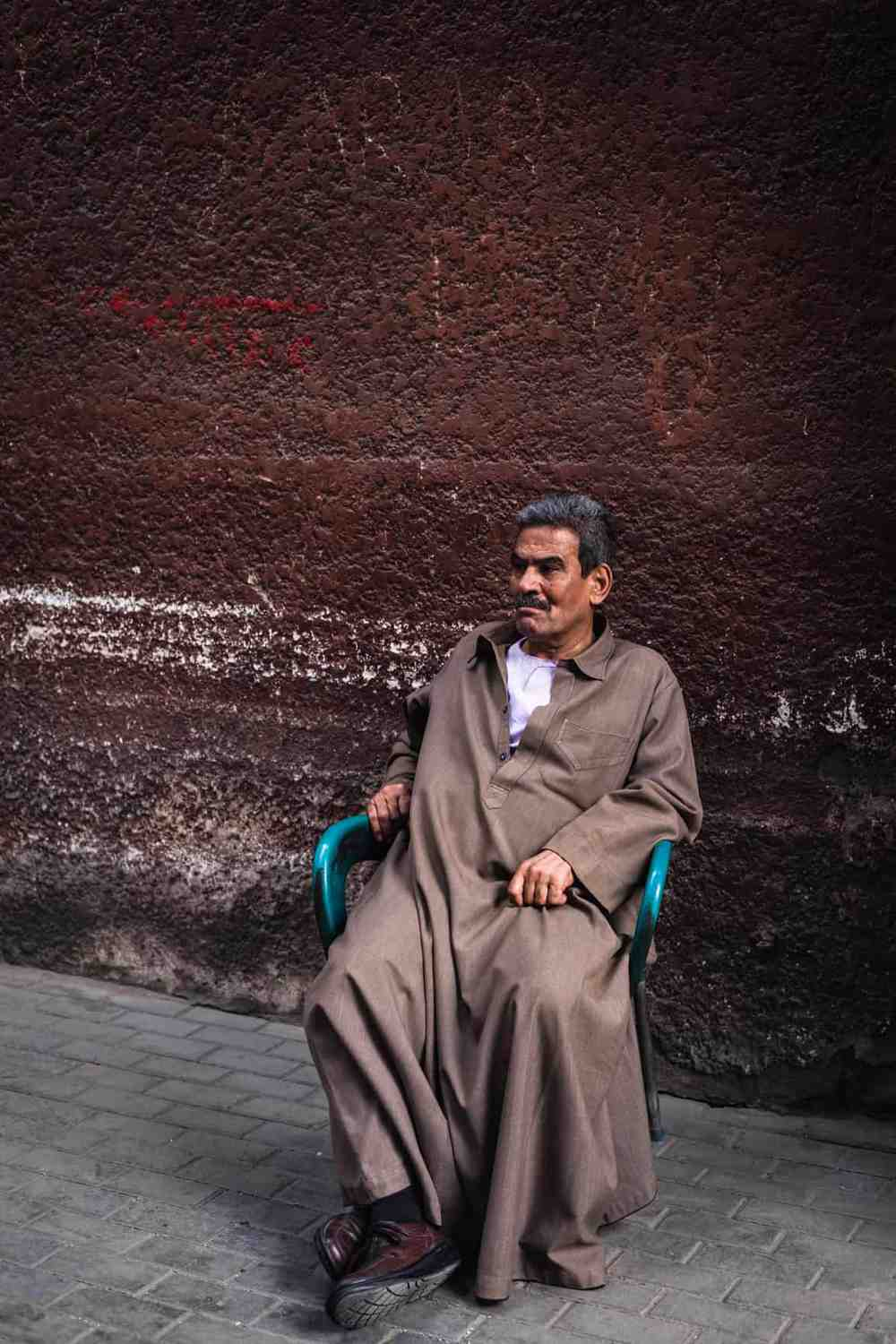 Man sitting in chair on the sidewalk in Cairo.