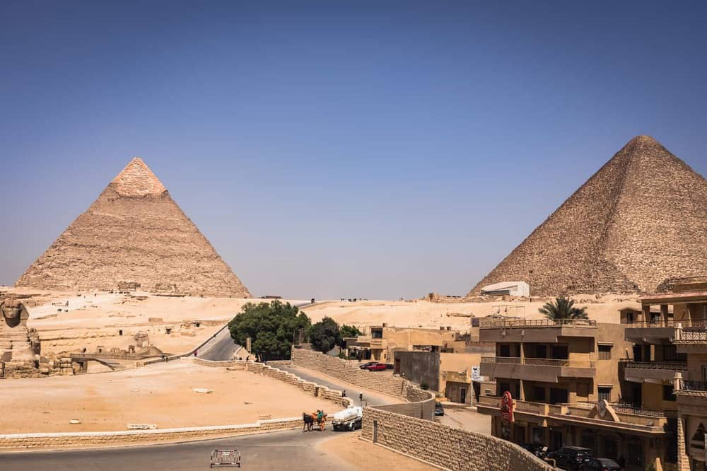 View of the Pyramids with a road with people, carts, and camels.