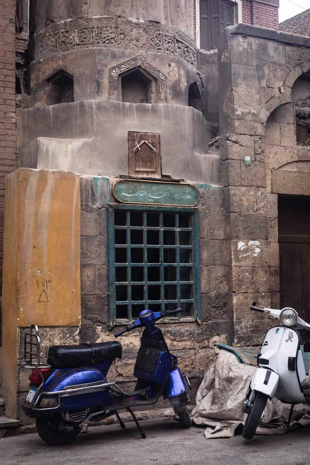 2 motorcycles parked outside an incredibly old building in Old Cairo.