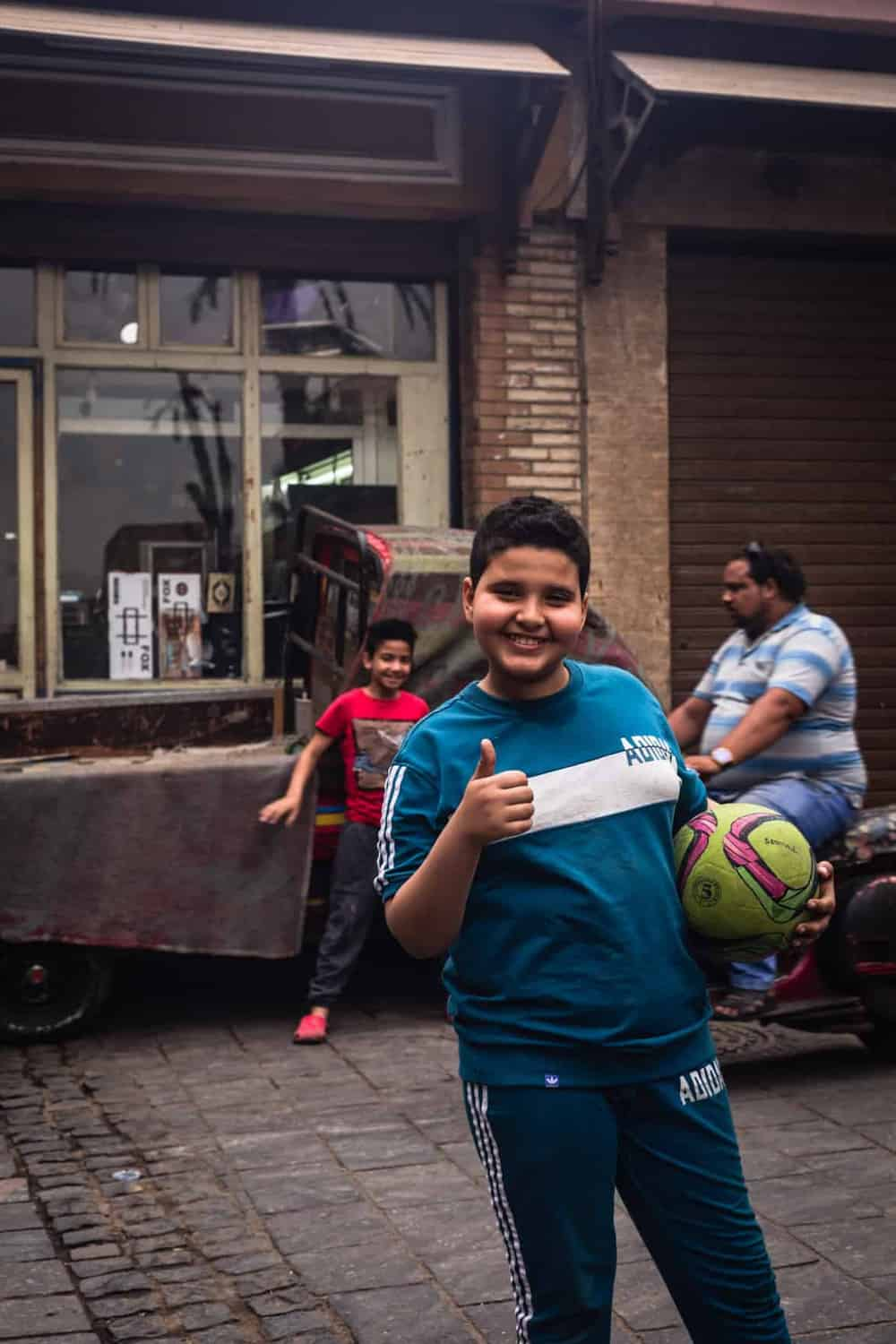 portrait shot of a kid holding soccer ball, posing with at thumbs up in Old Cairo.