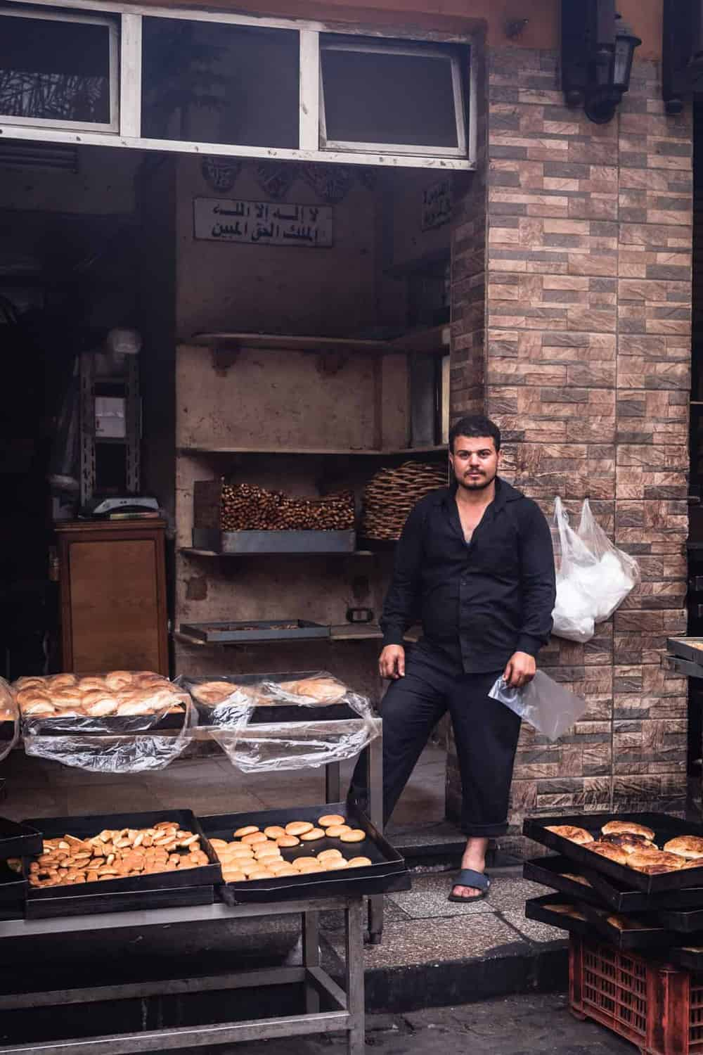Bakery in Old Cairo, portrait shot of store owner posing with a serious face in front if his baked goods.