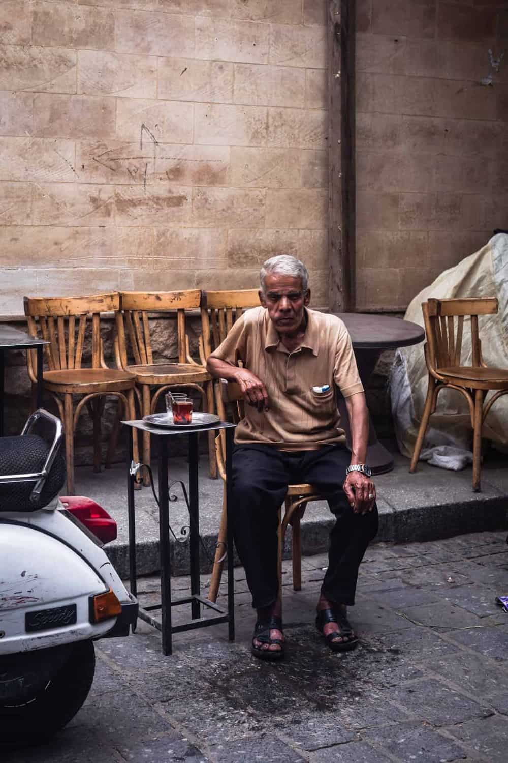 portrait shot of an old man sitting in a cafe in Old Cairo, posing for my camera.