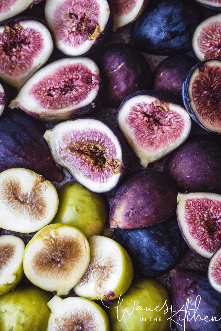 3 different varieties of figs, cut in half, up close. Over head shot. Can see the cut side of some on the skin side of others.