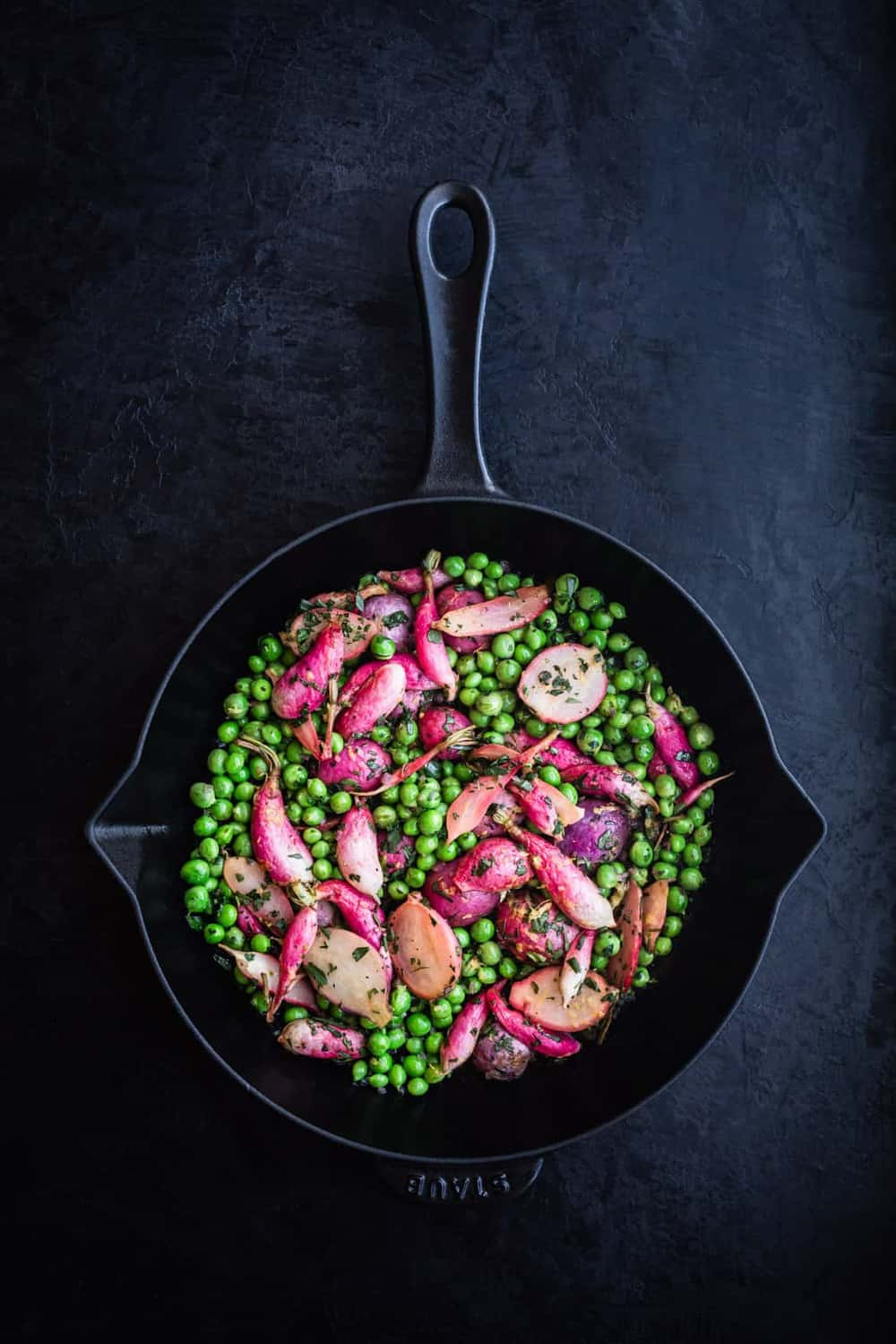 Cast iron skillet with peas and radishes mixed together and topped with tarragon.