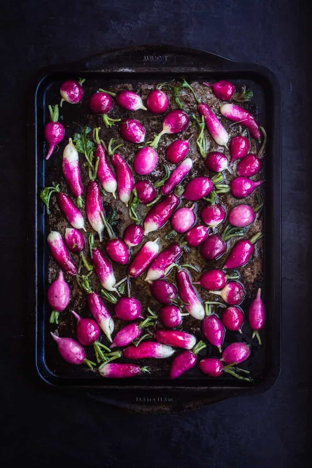 Raw radishes cut in half, tossed with dressing and on a baking sheet, cut side down on a black background. Overhead shot.