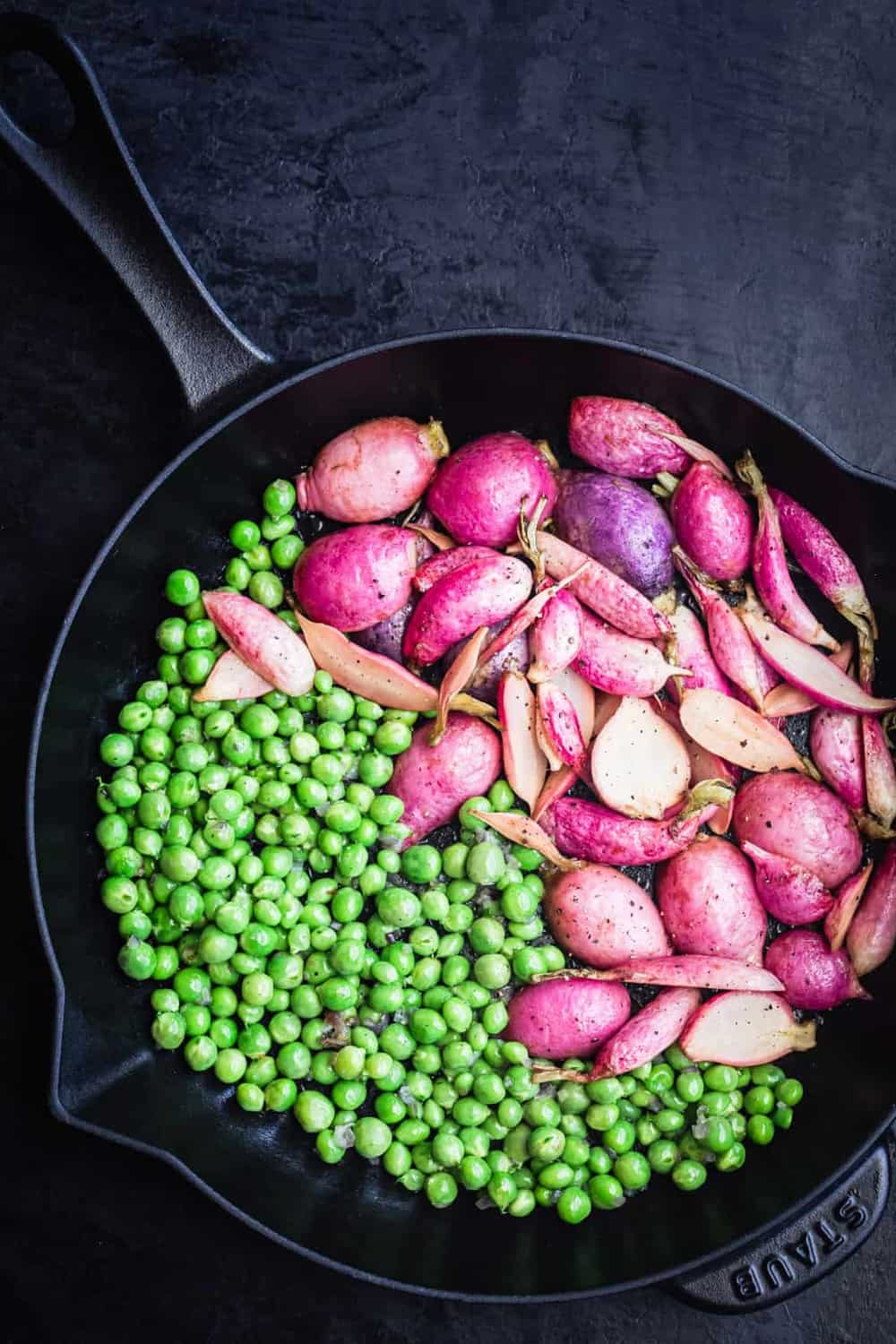 Cast iron skillet with peas on one half of the pan and roasted radishes on the other.