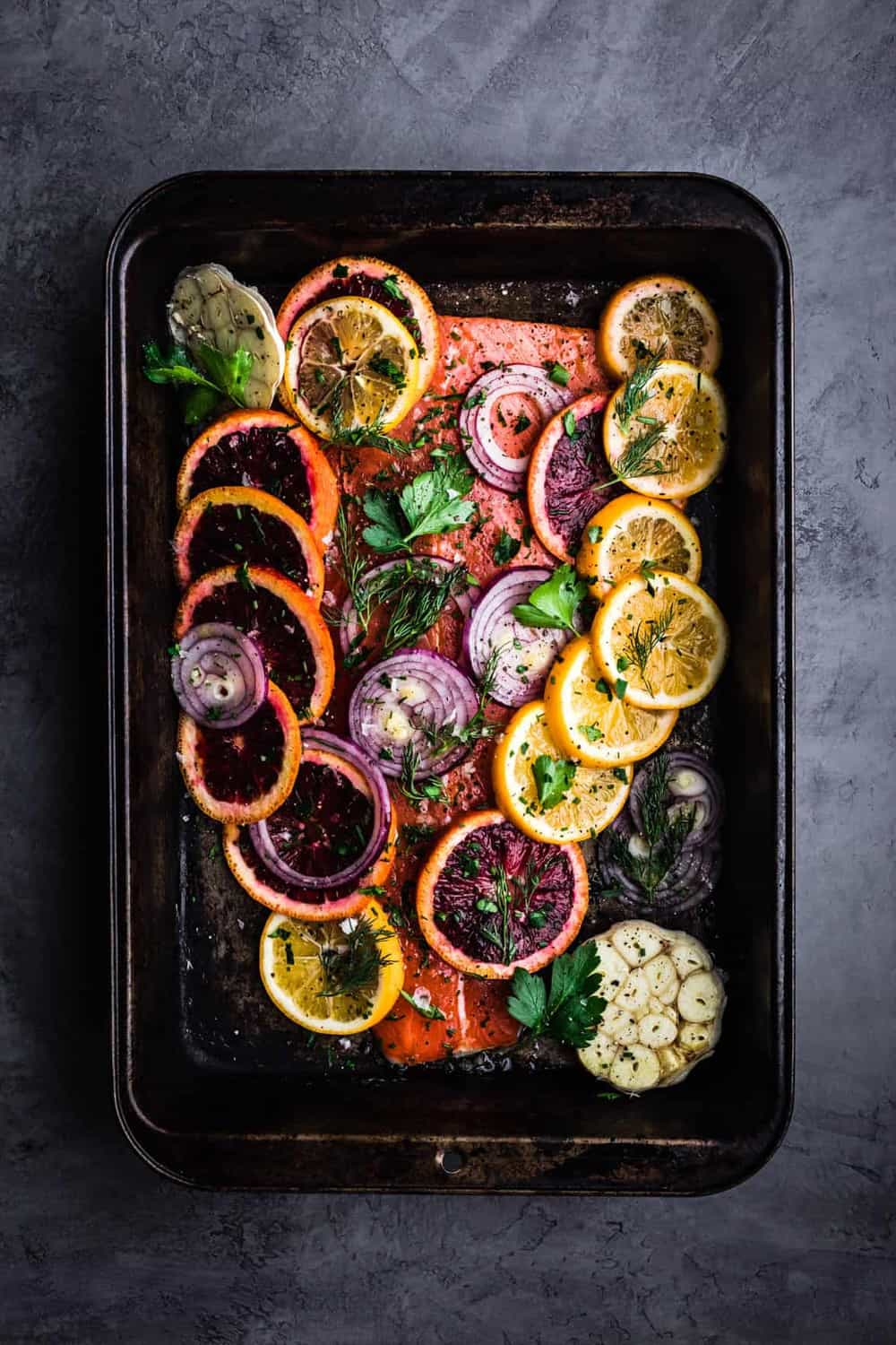 Fresh Citrus and Herb Roasted Salmon. Pre-oven with blood oranges, lemons, red onions, dill, parsley, salt and pepper on the salmon.
