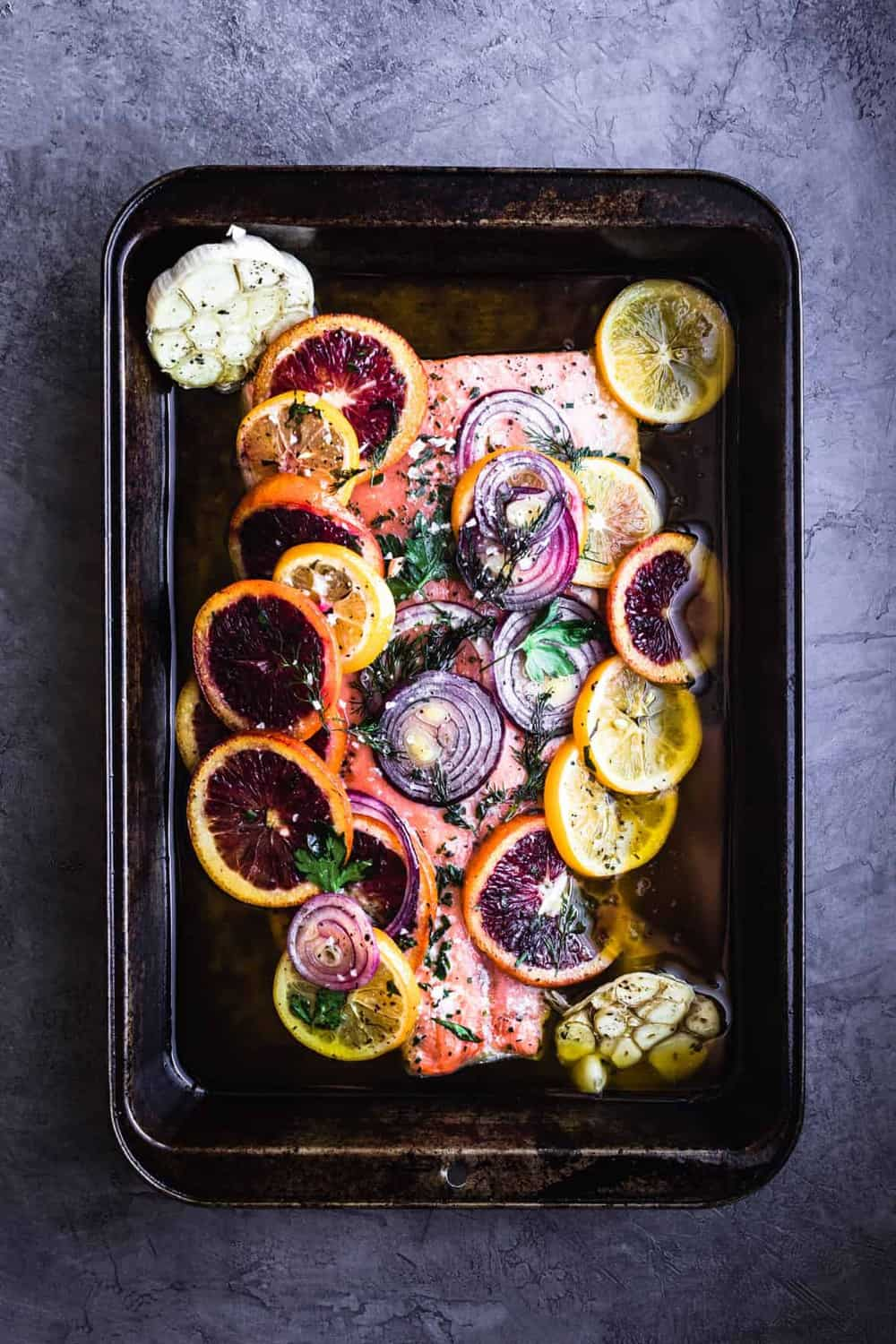 Fresh Citrus and Herb Roasted Salmon. Post-oven with blood oranges, lemons, red onions, dill, parsley, salt and pepper on the salmon.
