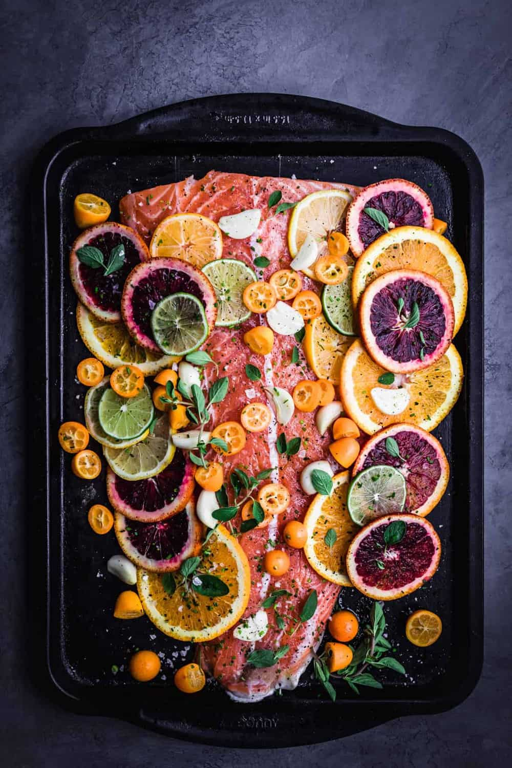 Citrus and Fresh Herb Roasted Salmon. Pre Oven with lemons, Meyer lemons, limes, blood oranges, oranges, kumquats, garlic and oregano on the salmon.