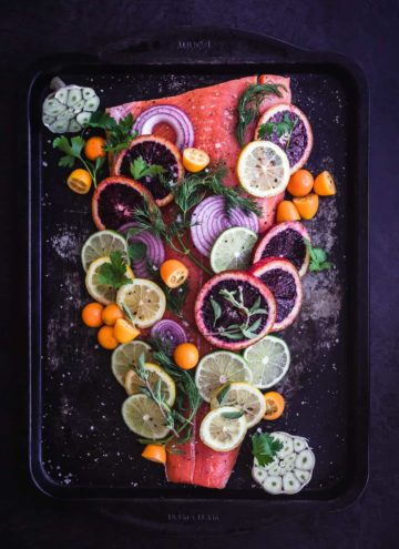 Citrus & Fresh Herb Roasted Salmon. Pre Oven with blood oranges, lemons, Meyer lemons, limes, kumquats, red onions, garlic, parsley, and dill on the salmon.