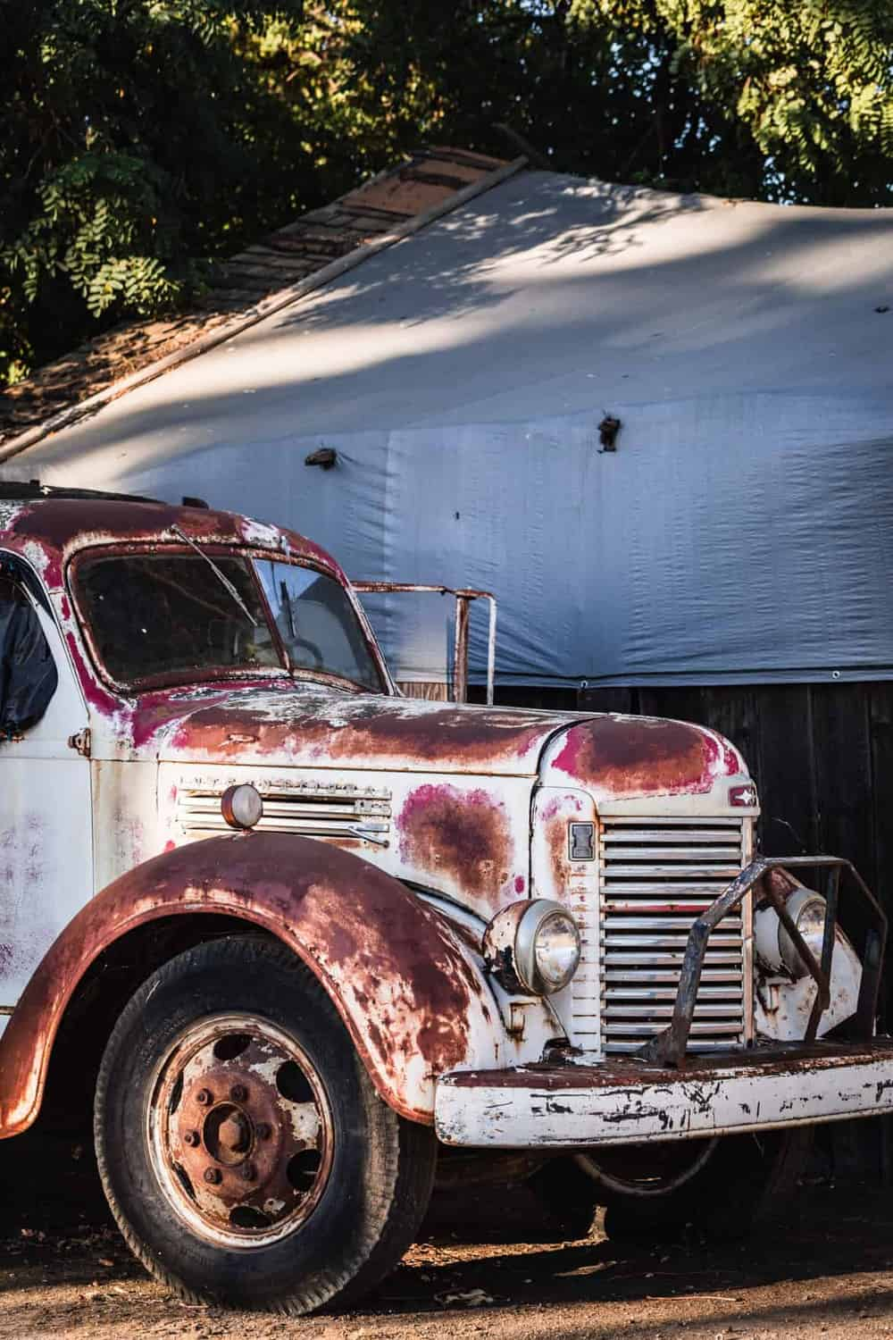 A very old truck by the farm.