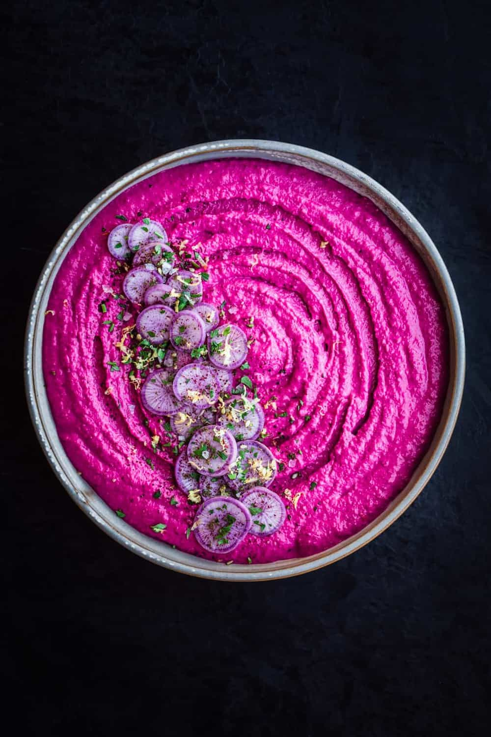 Beet Hummus with Ninja Radishes, Parsley, Lemon Zest, Sumac & Flaky Sea Salt in a white bowl, overhead shot on a black background.