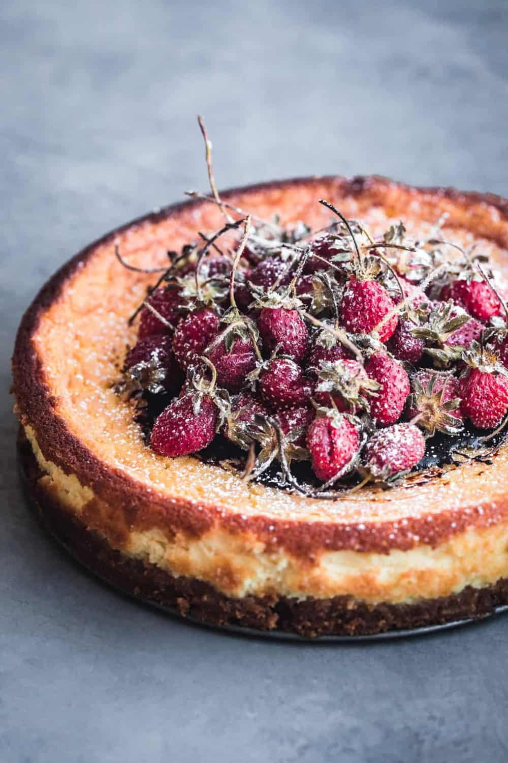 Mascarpone Cheesecake with balsamic roasted long stemmed strawberries, out of the spring form pan, 45 degree angle shot.