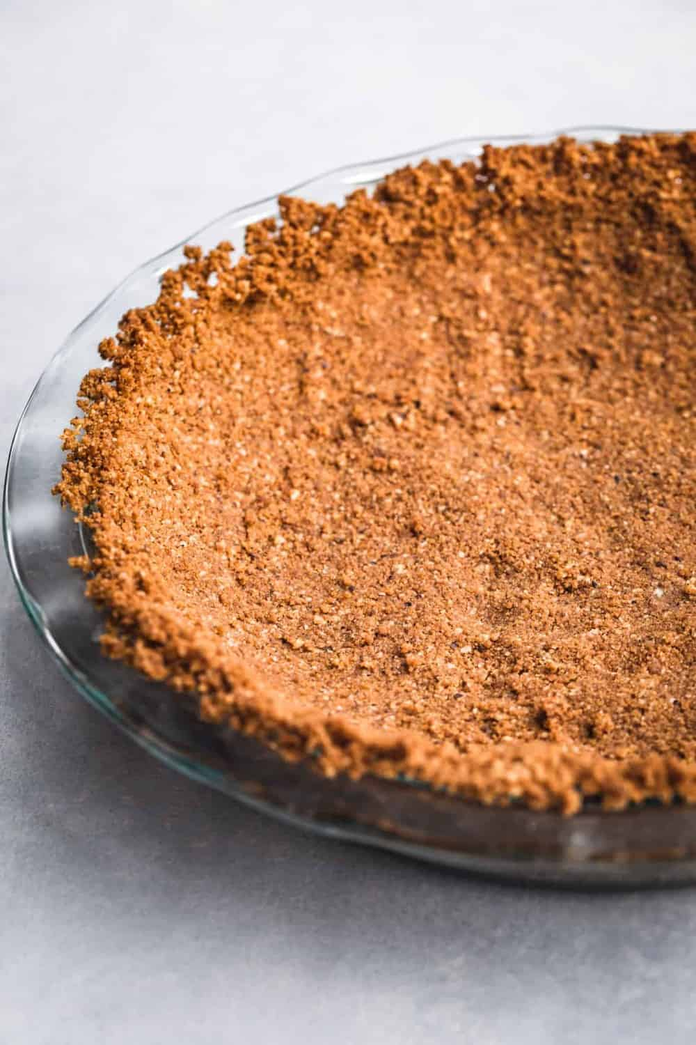 Gingersnap crust. Post oven and still empty. Side angle shot on a white background. Left side cut off.
