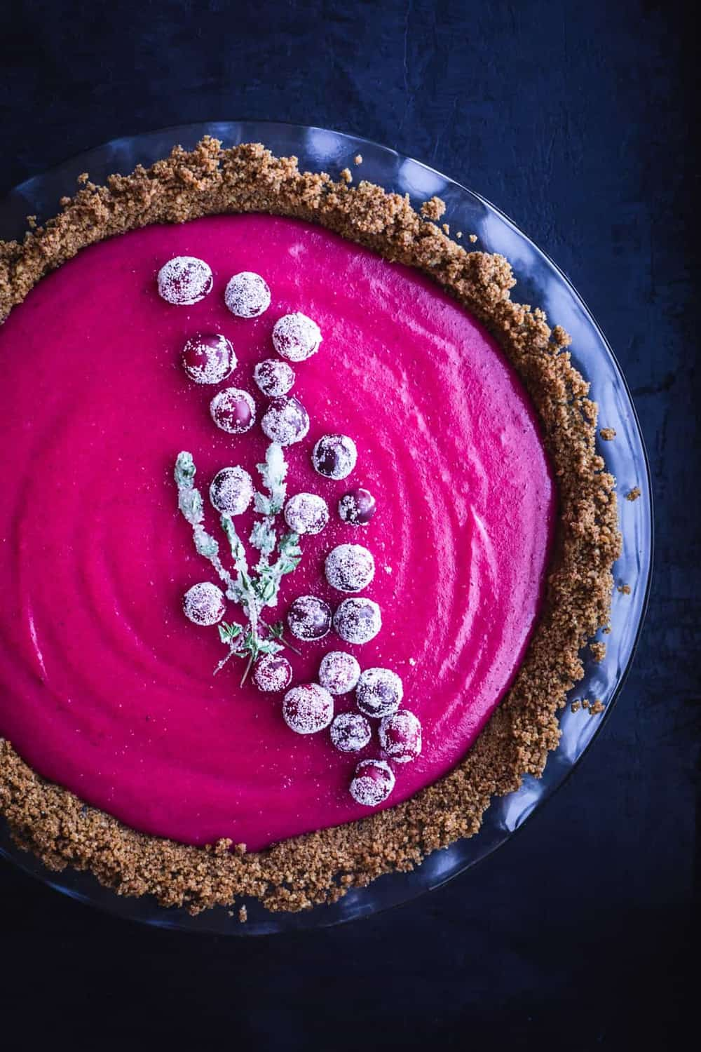 Cranberry Gingersnap Pie. Topped with sugared cranberries and sugared thyme. overhead shot, on a black background, left side cut off.