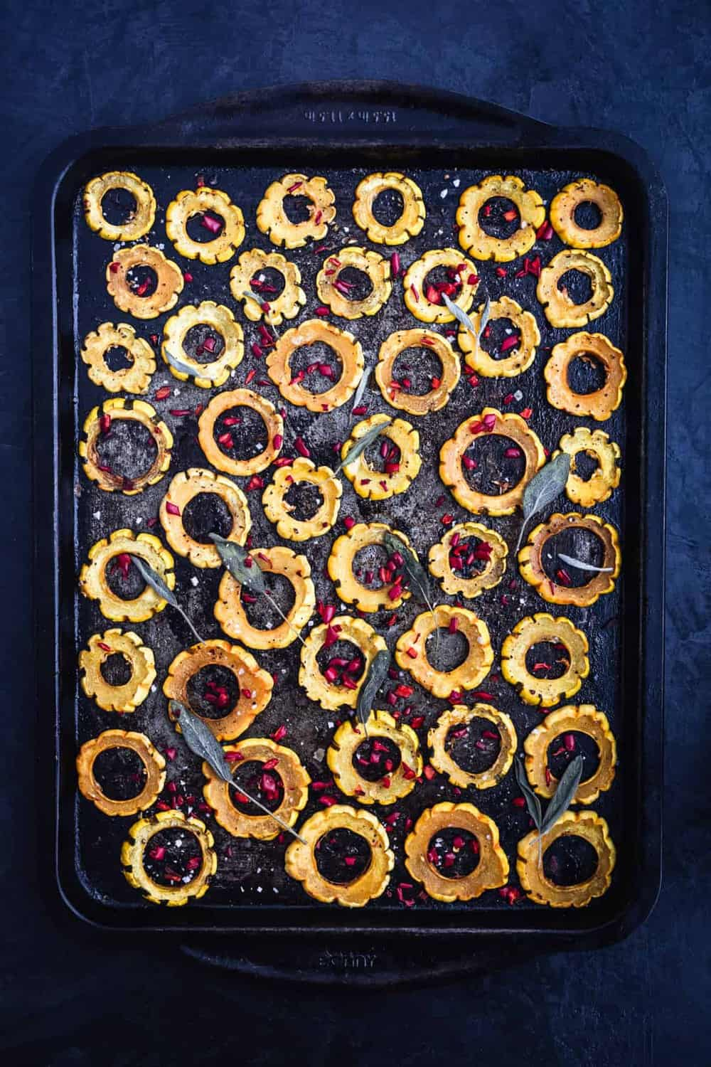 Sliced roasted squash rings on baking sheet, can see entire sheet, topped with fresh sage leaves. Pre Oven.
