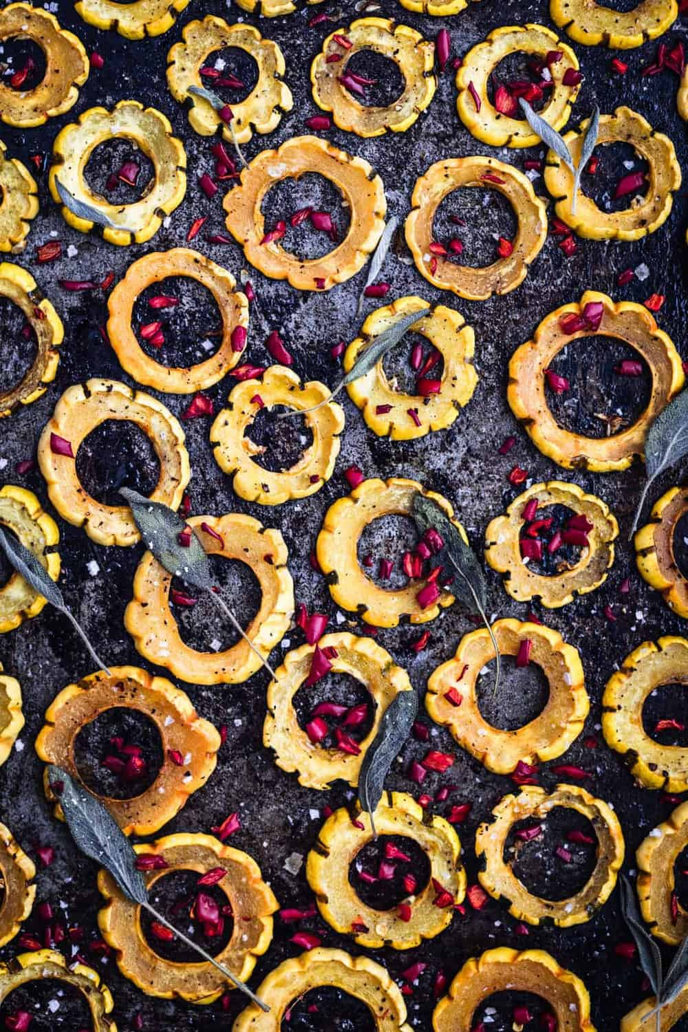 Sliced roasted squash rings on baking sheet, topped with chilies and fresh sage leaves, up close. Post-oven.