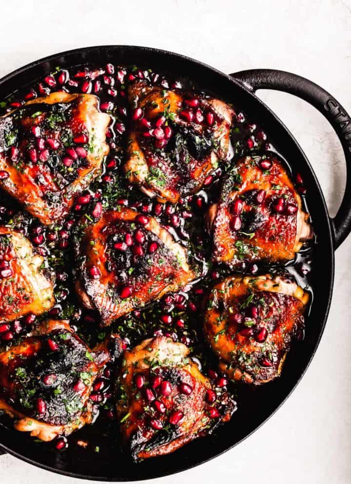 Pomegranate Chicken topped with pomegranate arils and parsley, in cast iron skillet on a white background; overhead shot.