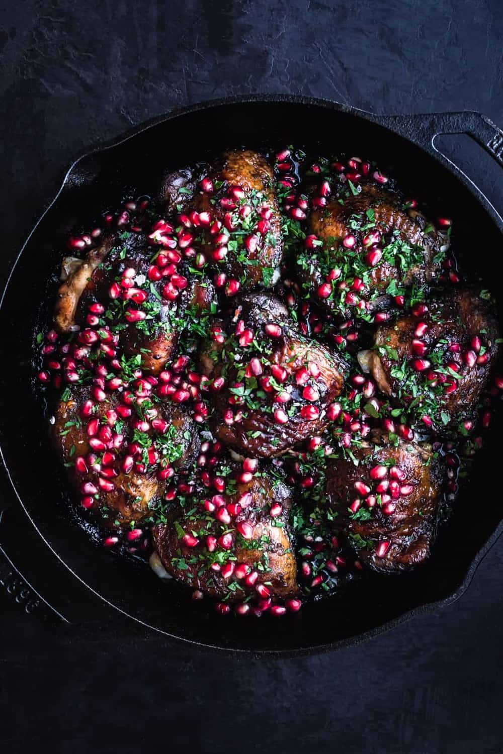 Pomegranate Skillet Chicken, out of the oven and all done, in a cast iron skillet on a black background. Over head and center frame shot.
