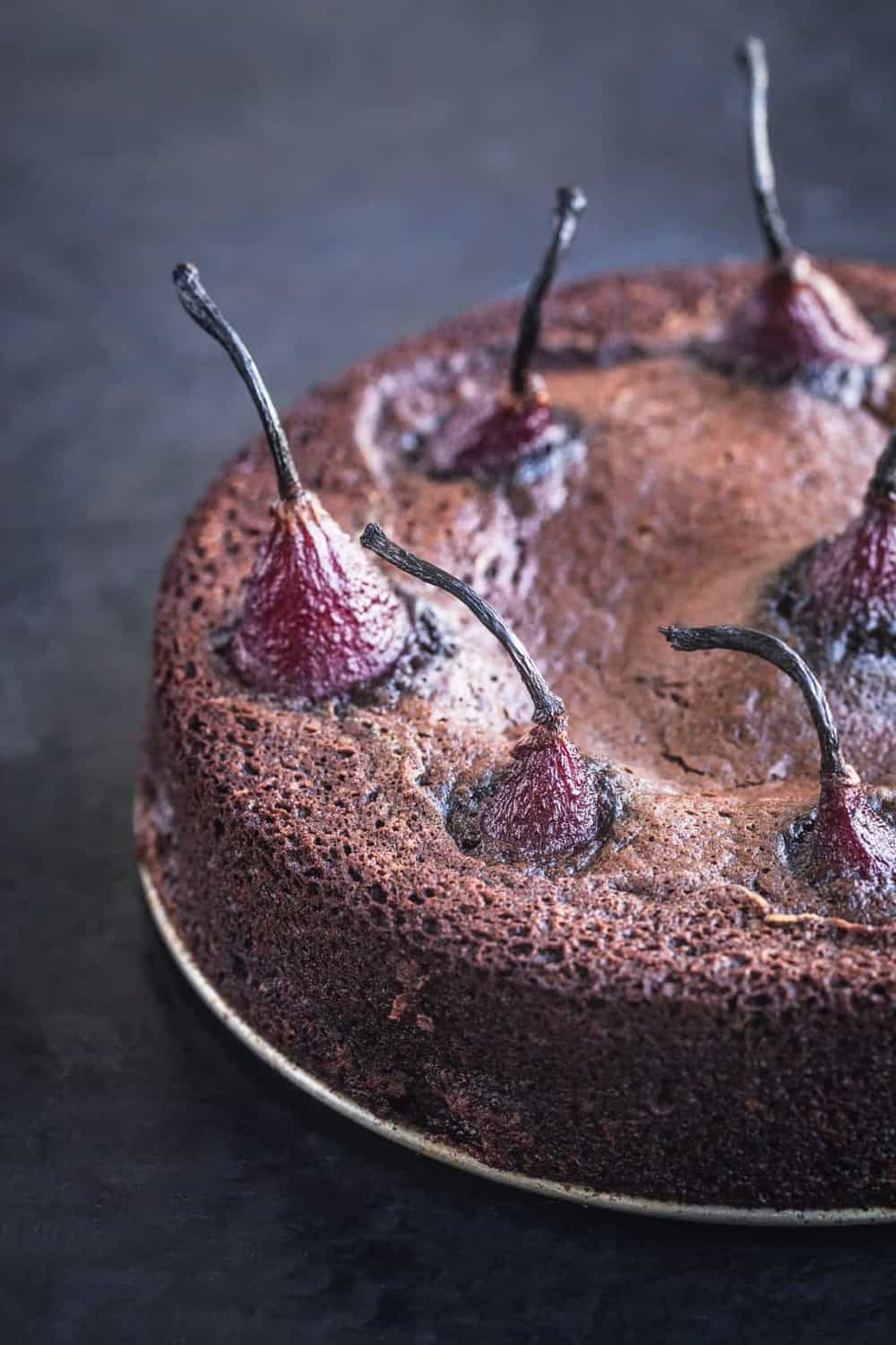 Spiced red wine poached pears in chocolate cake batter, post oven and out of springform pan. Side angle , 45 degree shot, right side of cake is cut off, on a black background.