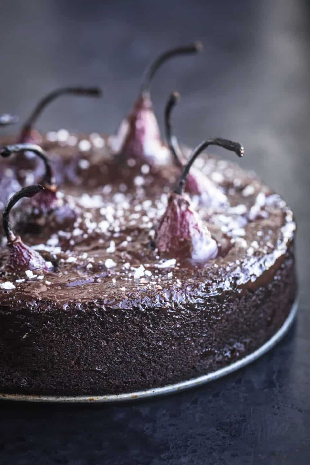 Spiced red wine poached pears in chocolate cake batter, out of cake pan, post oven, topped with ganache and flaky sea salt. Side angle shot, on a black background, left side if cut off.