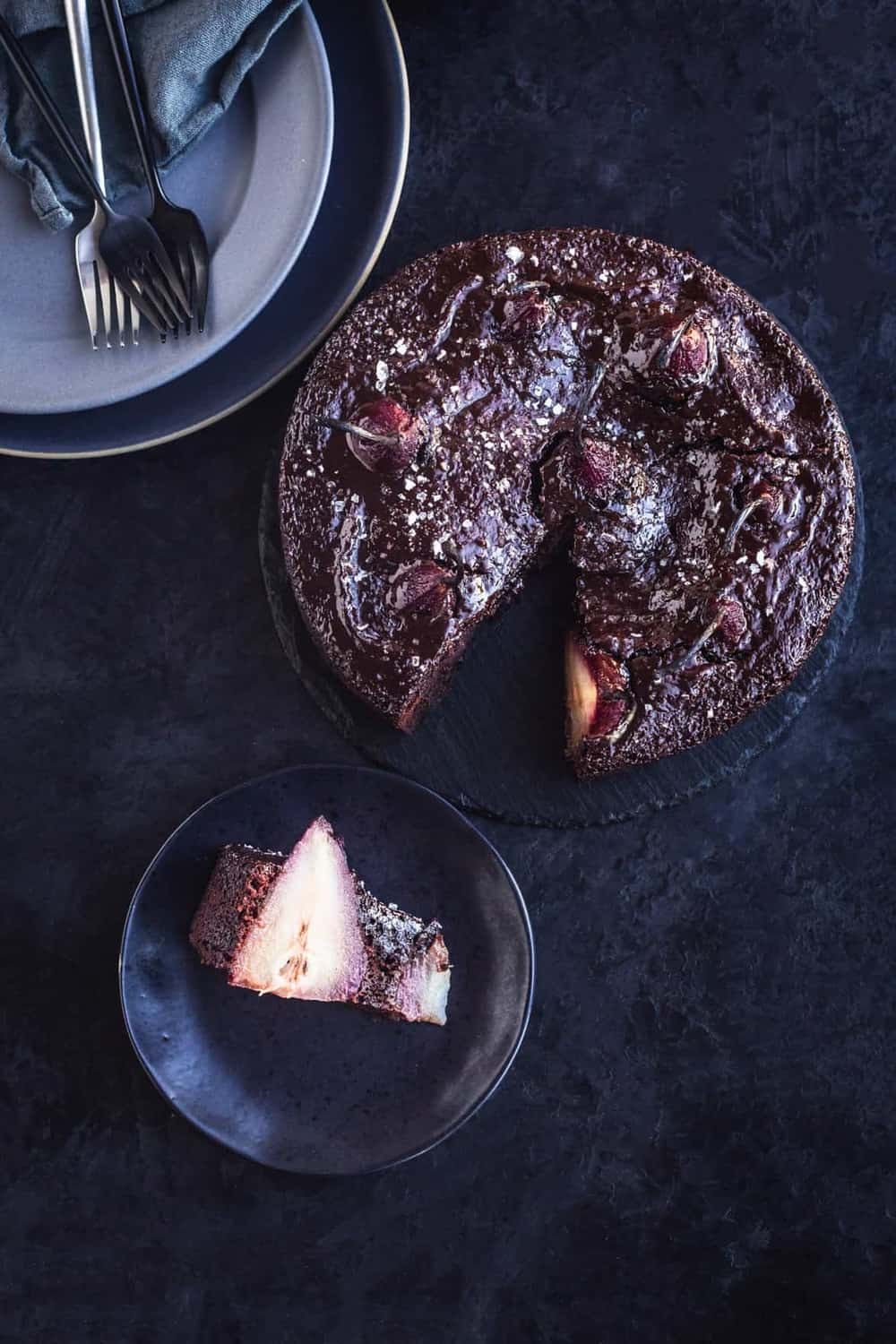 Spiced red wine pear and chocolate cake tablescape. The cake is cut into, with a piece served on a plate, with other plates, utensils and the rest of the cake in the frame, on a black background.