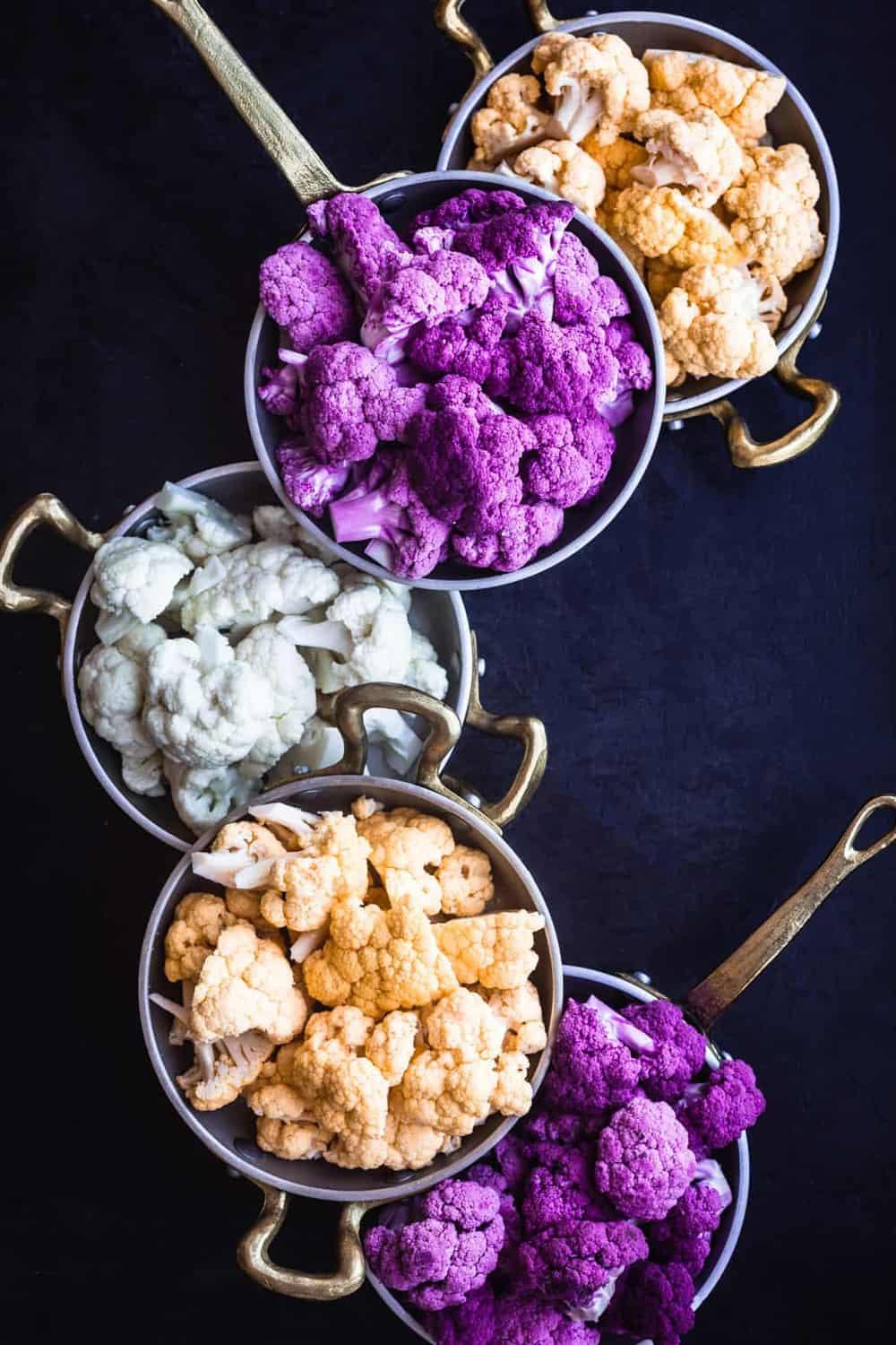 Purple, Yellow/Orange and White Cauliflower cut into florets and separated by color, into 5 little pans (2 of purple, 2 of yellow/orange and 1 white) on a black background.
