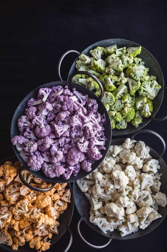 Yellow/Orange, Purple, White, and Green Cauliflower, each cut into florets and separated by color into 4 silvers bowls with handles, on a black background.