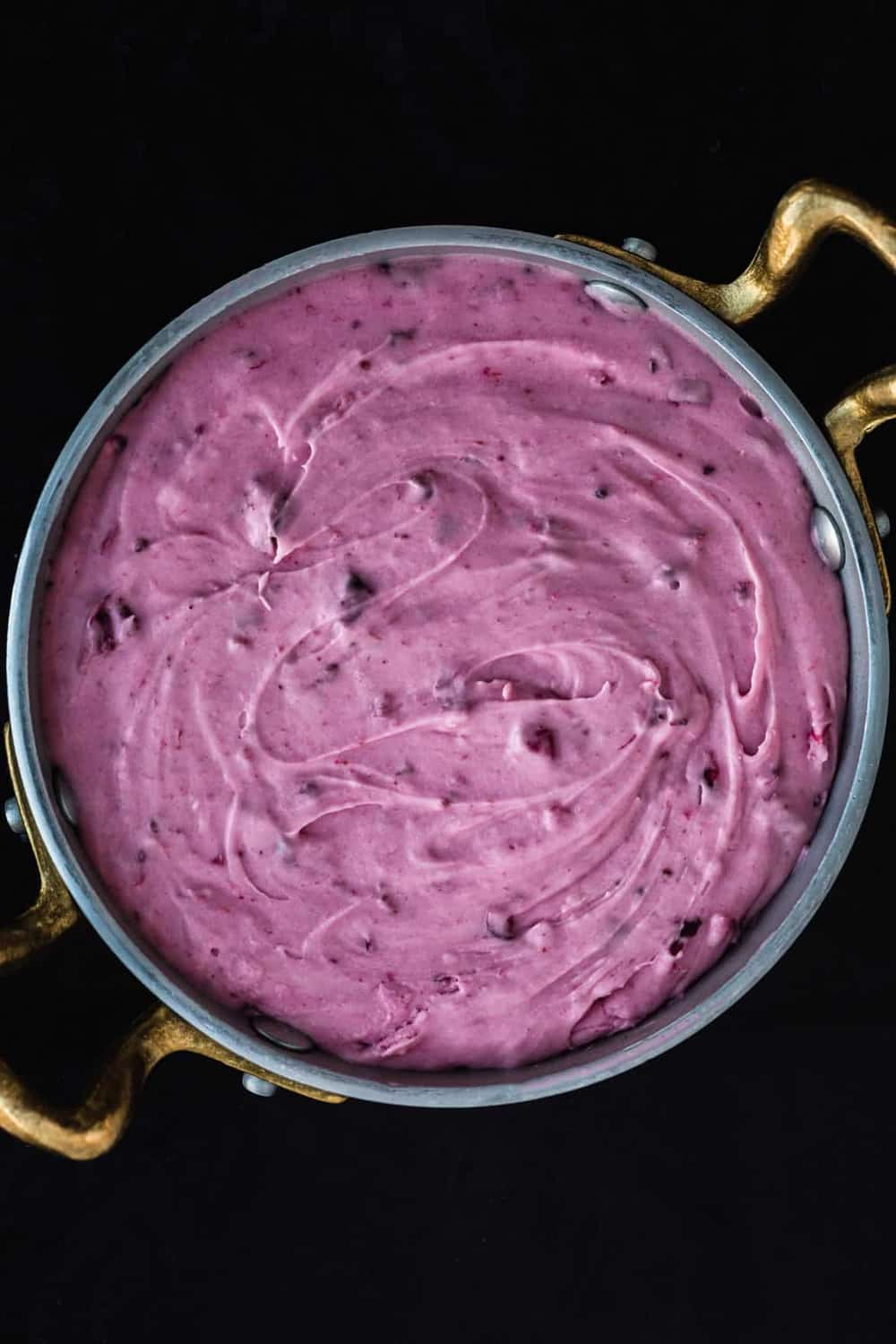 The cranberry cream cheese, in a silver bowl with gold handles, overhead shot on a black background.