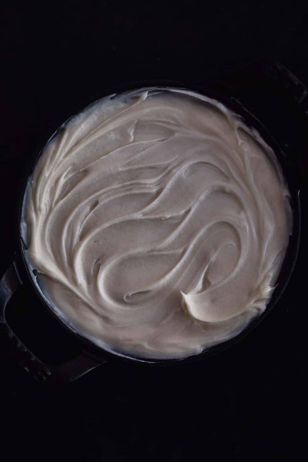 The vanilla mascarpone filling, in black bowl with black handles, on a black background. Overhead shot.