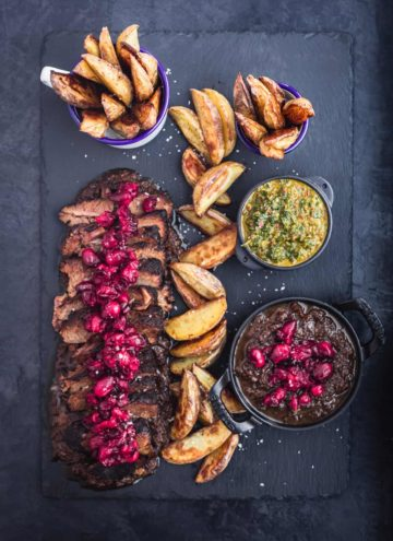 Thinly sliced brisket on a black slate with cranberry sauce on top, baked wedge potatoes and 2 little bowls of chimichurri and more cranberry sauce. Overhead shot on a back background.