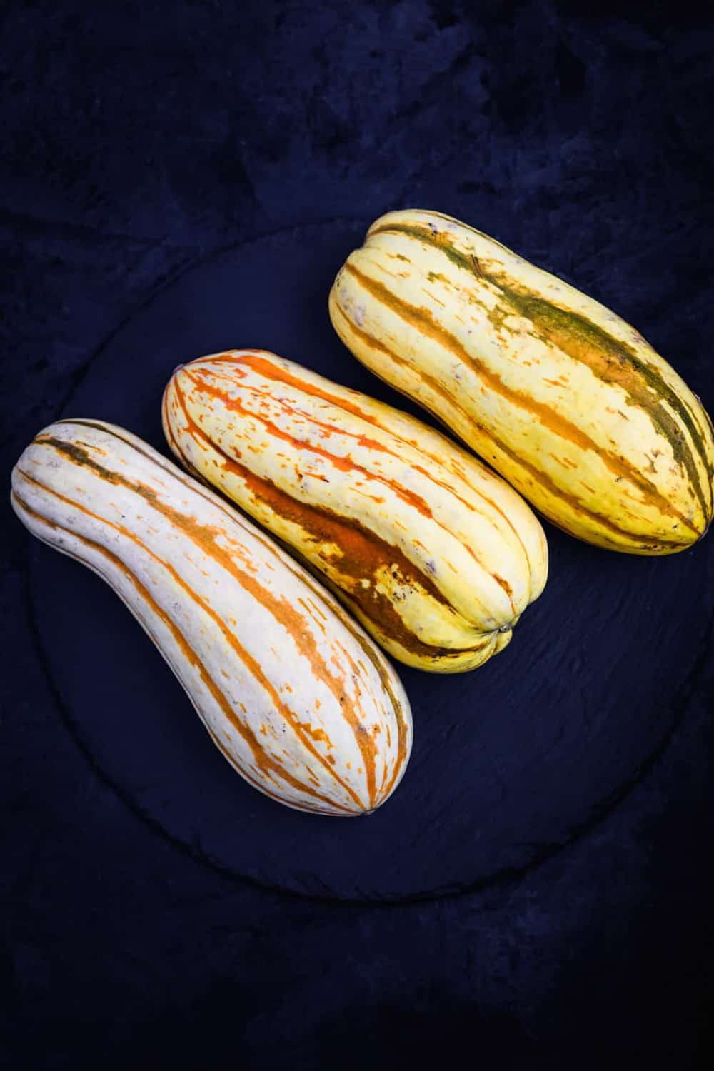 3 whole Delicata Squashes, on a black slate, on a black background. Overhead shot.