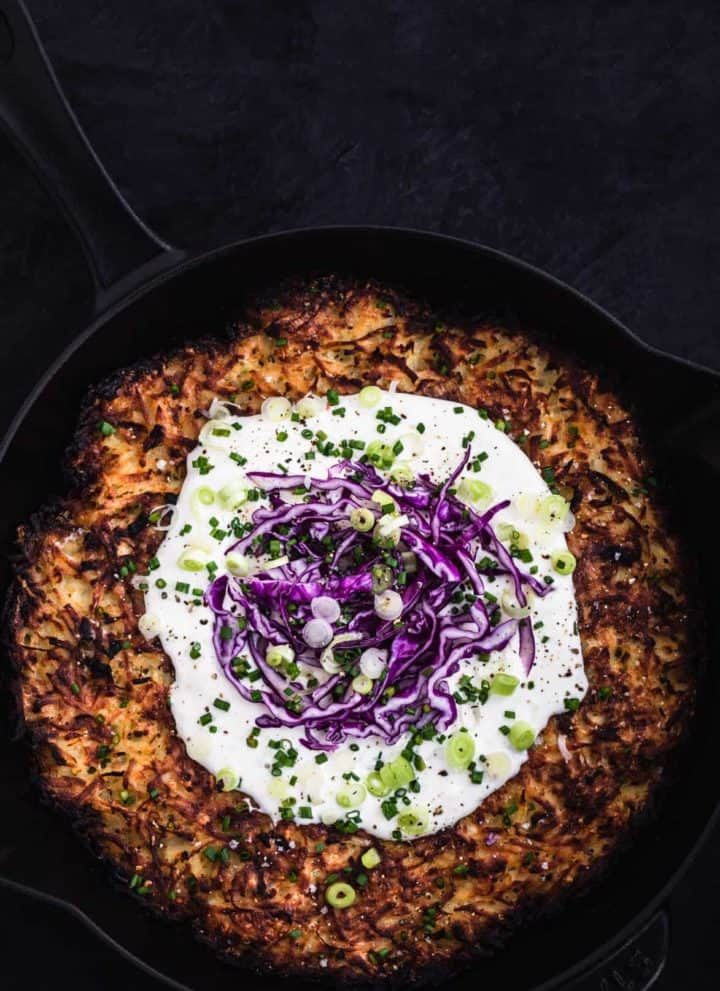 Giant skillet latke in pan with sour cream, purple cabbage, scallions and chives.