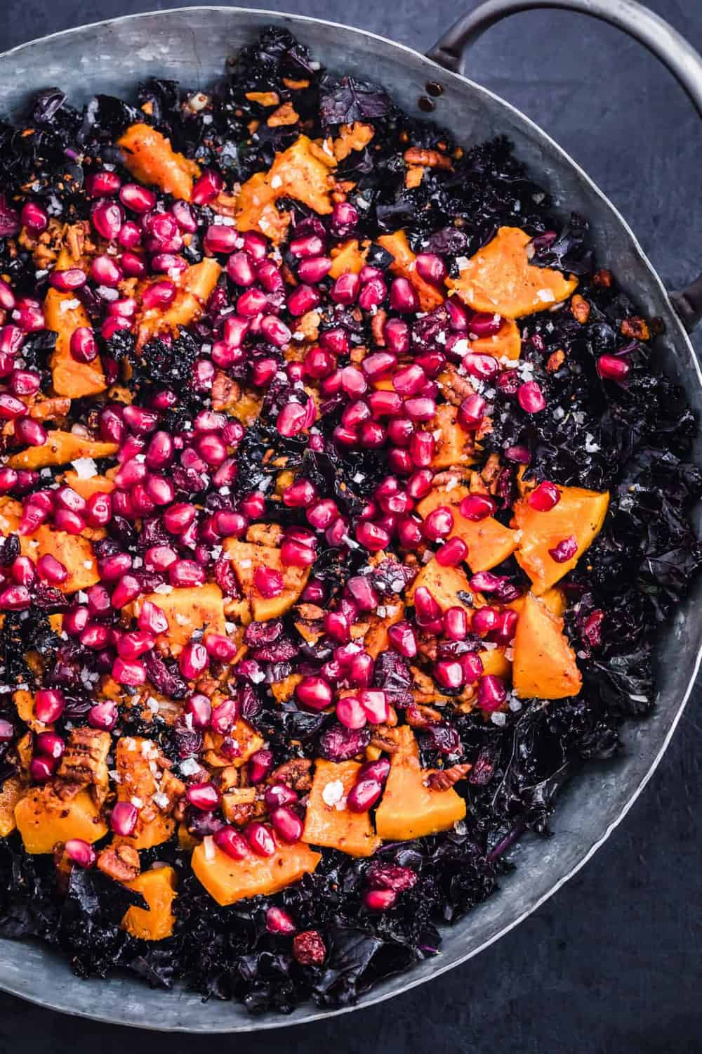 The final assembled salad with kale, squash, pecans, cranberries and pomegranates in a silver serving bowl.