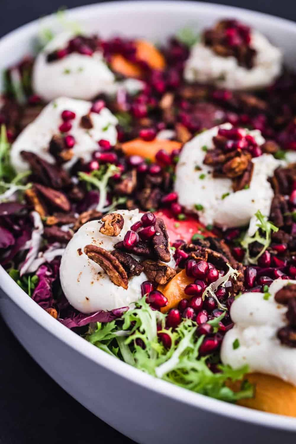 Burrata on top of frisee and radicchio with pears, persimmons, pomegranate and pecans scattered on top a serving plate.