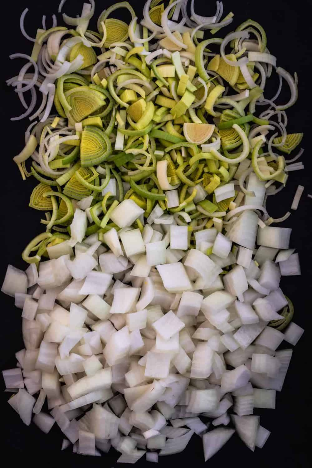 Leek and onion all cut up, overhead shot.