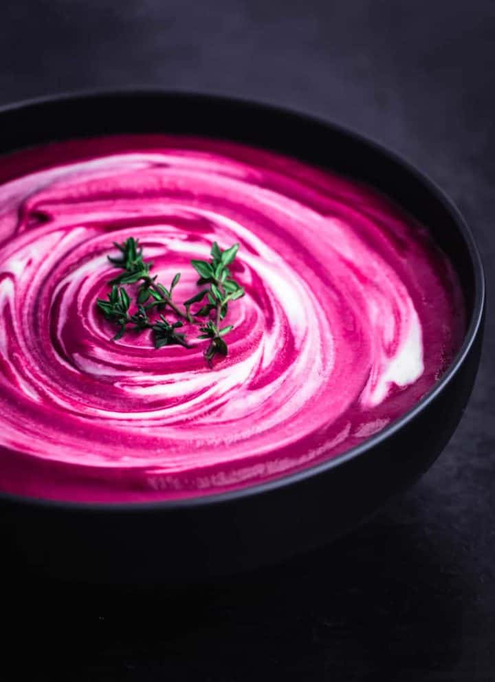 Roasted Beet Soup with Cashew Cream swirl and thyme sprigs, side angle shot on a black background.