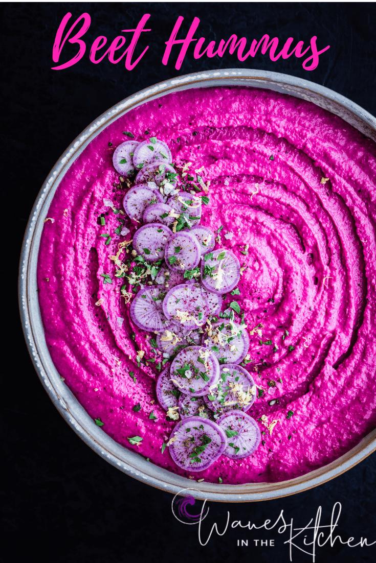 Beet Hummus with Ninja Radishes, Parsley, Lemon Zest, Sumac & Flaky Sea Salt in a white bowl. Overhead shot.