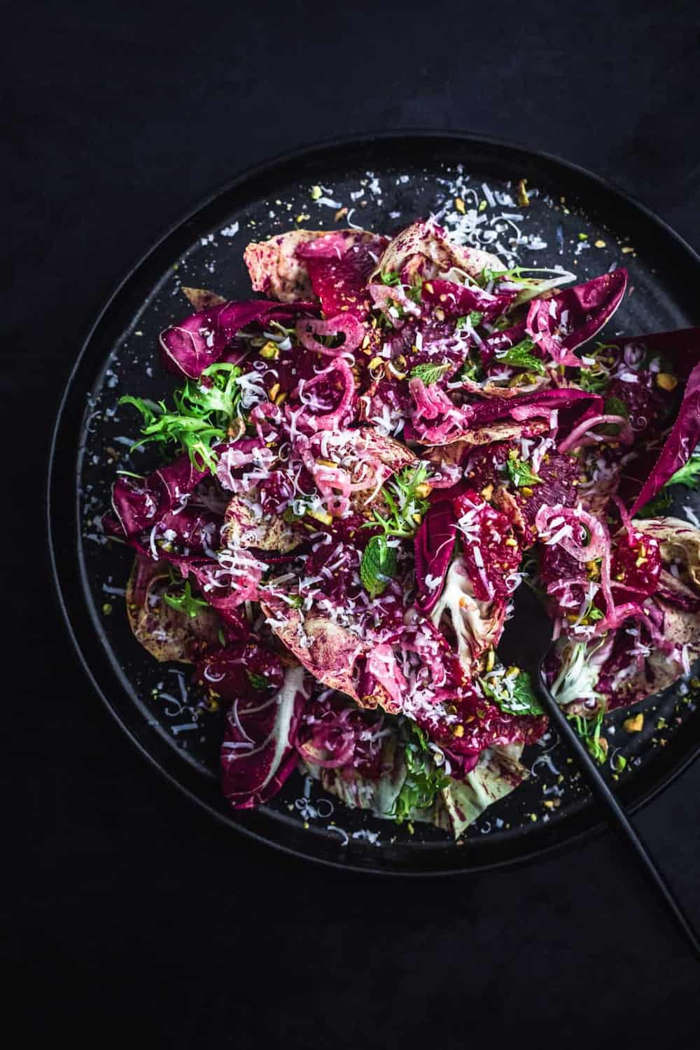 Blood Orange and fennel salad with chicories, pistachios, shredded cheese, mint and shallots on a black plate with a fork.