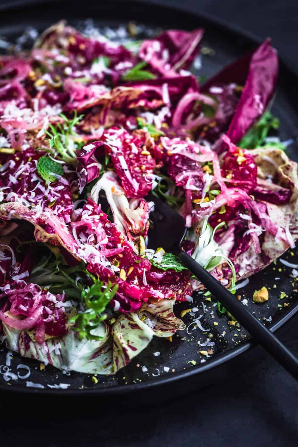 Blood Orange and fennel salad with chicories, pistachios, shredded cheese, mint and shallots on a black plate with a fork. Up close side angle shot.
