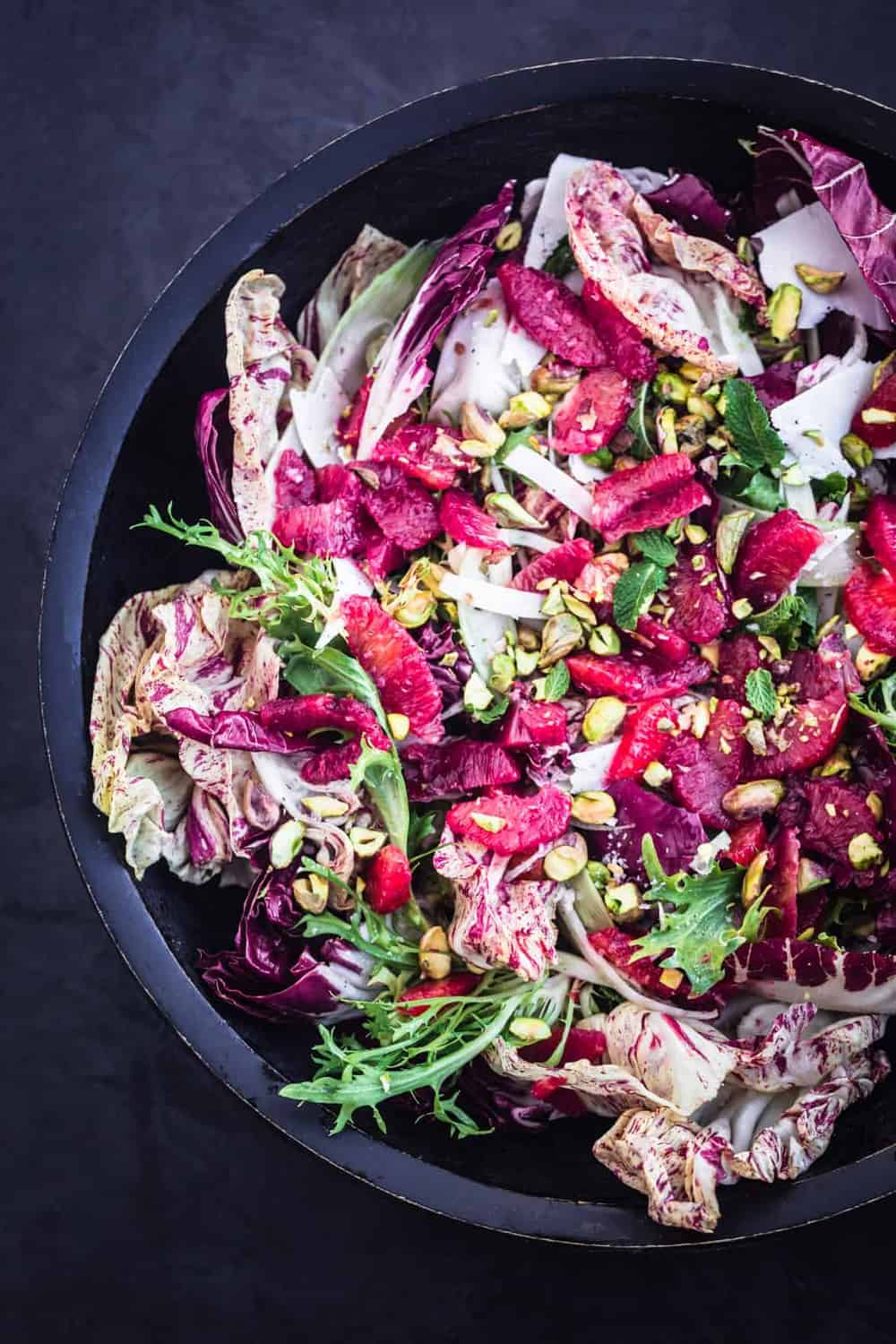 Blood Orange & Fennel Salad with chicories, ricotta salata, pistachios and mint in a large dark bowl.