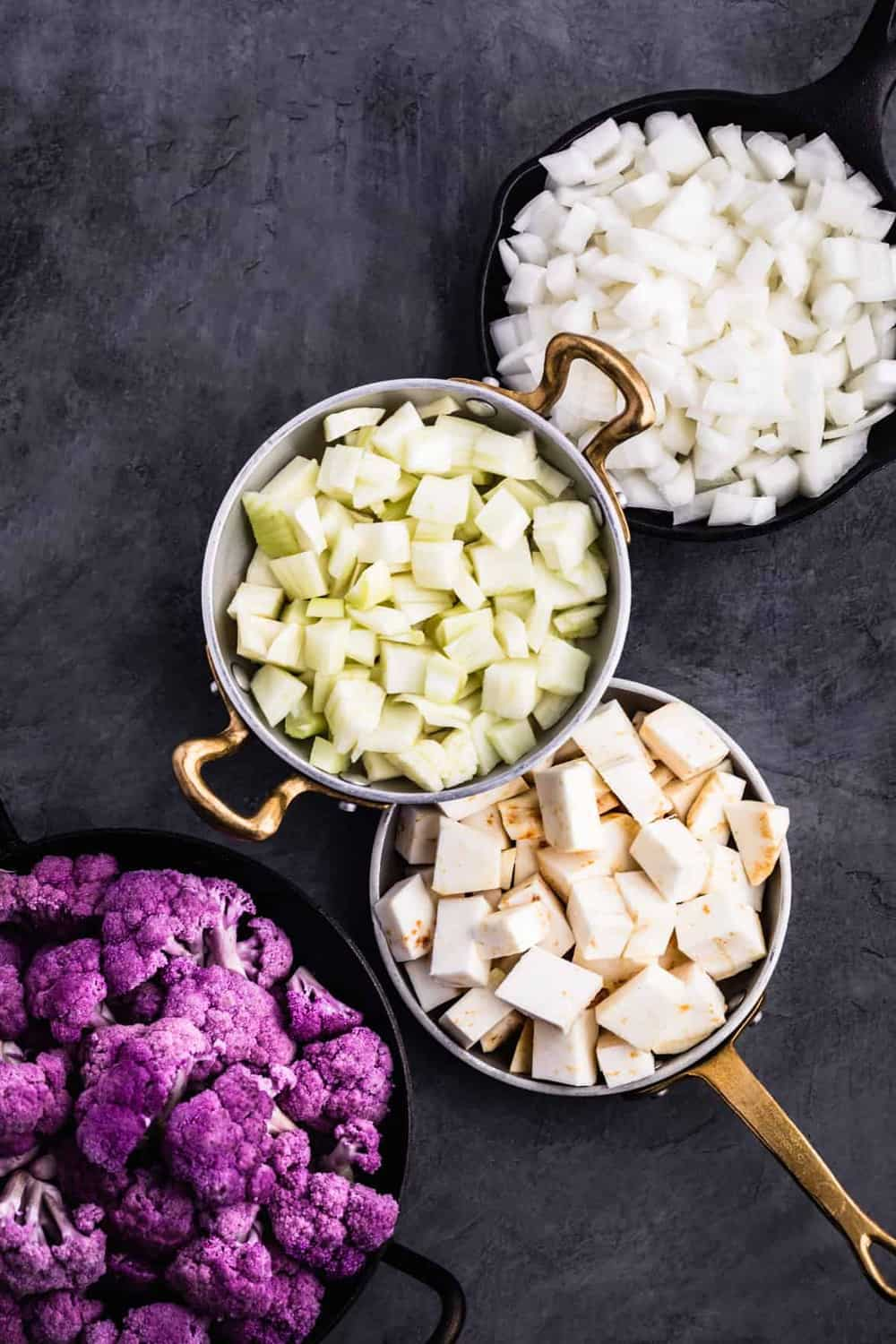 Ingredient prep shot with the cut up cauliflower, onions, celery root and fennel.