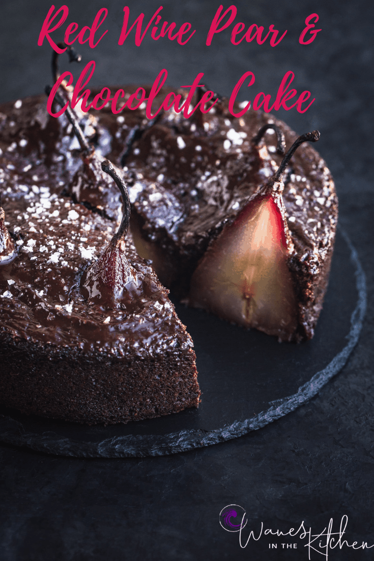 Spiced red wine poached pears in chocolate cake batter, out of cake pan, post oven, topped with ganache and flaky sea salt. Side angle shot. Cake is cut into and can see a full pear sliced, on black background, and left side of cake is cut off.