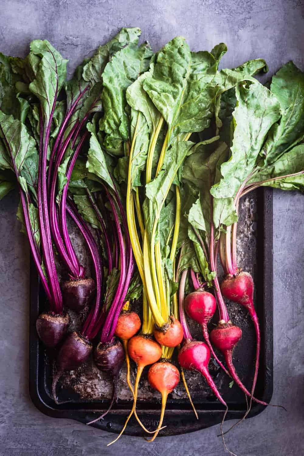 Golden, red and purple beets on a baking sheet with their leafy green tops.